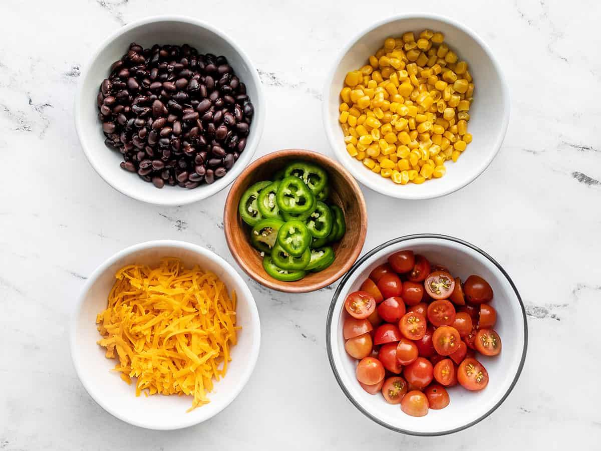 coberturas de salada de taco de peru em tigelas: feijão, milho, queijo, tomate, pimenta jalapeño