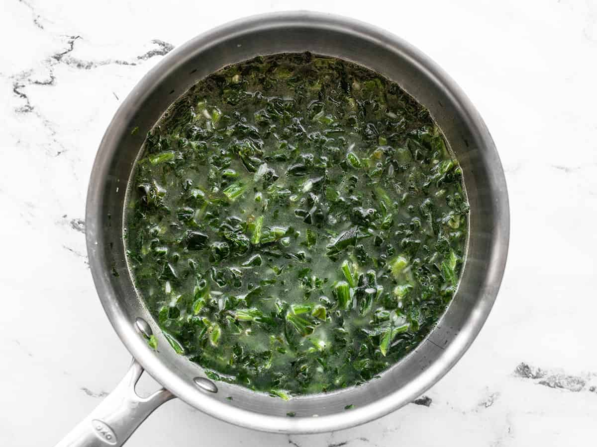 Stirred rice spinach and water in the saucepot
