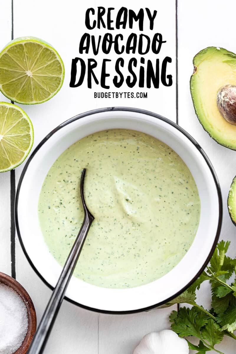 Creamy avocado dressing in a bowl with a black spoon, title text at the top