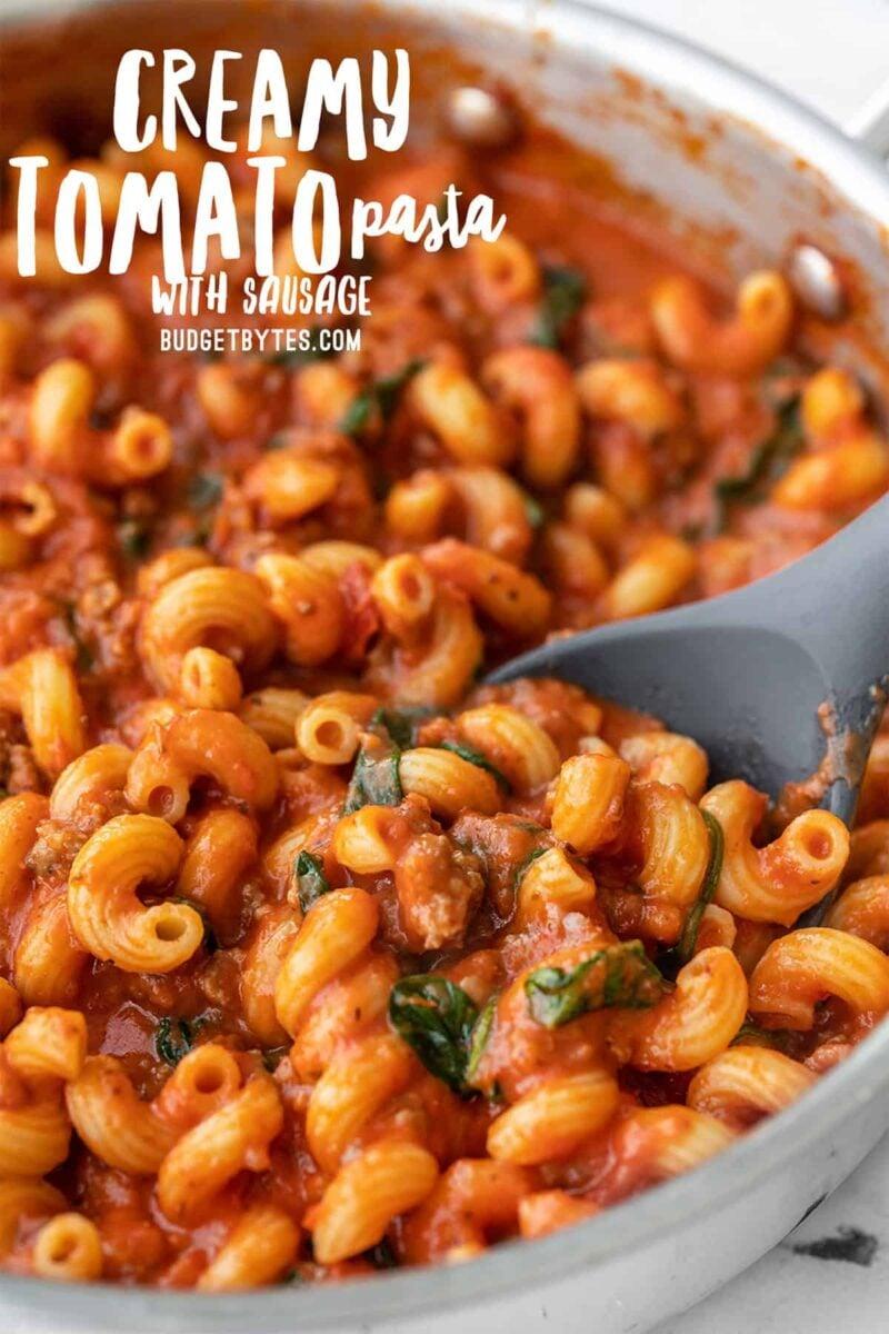 Close-up vista lateral de massa cremosa de tomate com salsicha, texto do título no topo