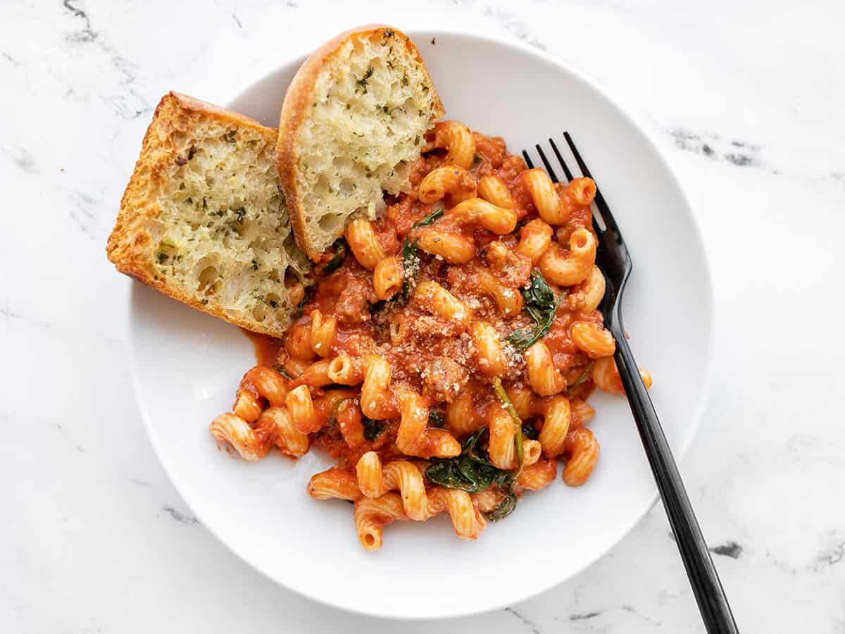 A bowl full of Creamy Tomato Pasta with Sausage with garlic bread and a fork