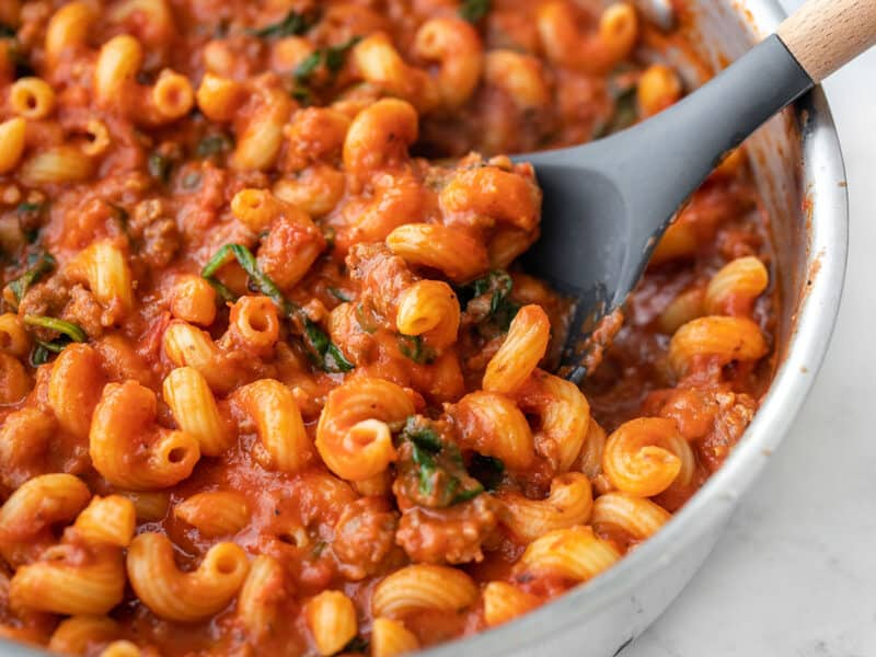 Close up side view of a skillet full of creamy tomato pasta with sausage