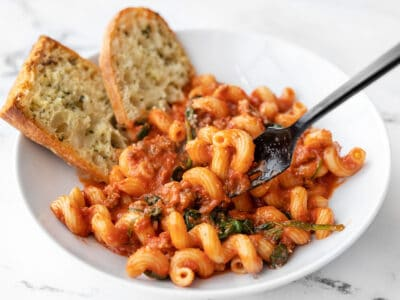 front view of a bowl full of creamy tomato pasta with sausage, a bit lifted on the fork