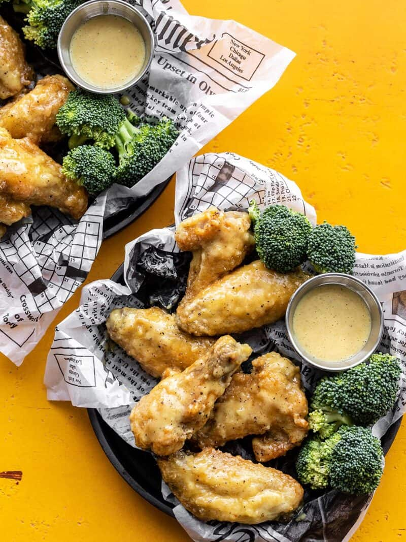 Two trays with honey mustard wings, broccoli, and cups of sauce