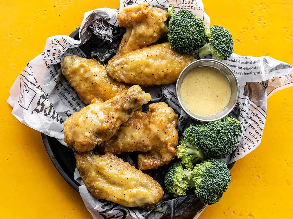 Overhead view of honey mustard wings on a tray with broccoli and a cup of sauce