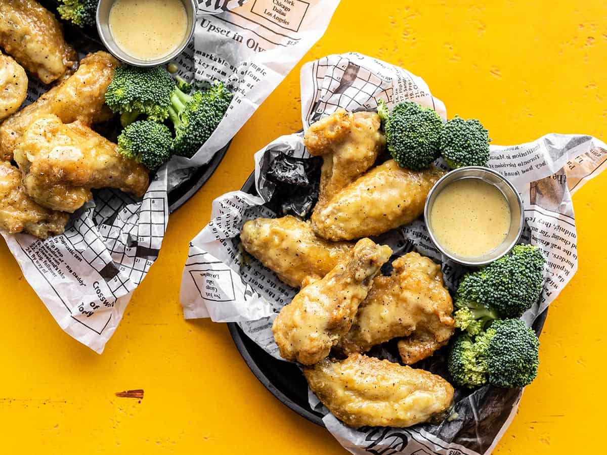 Two trays of honey mustard wings with broccoli and sauce