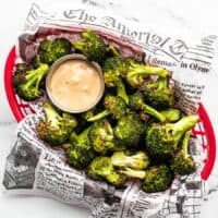 Overhead view of a basket full of oven roasted broccoli with dipping sauce