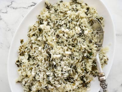 Close up overhead view of spinach rice with feta in a serving dish