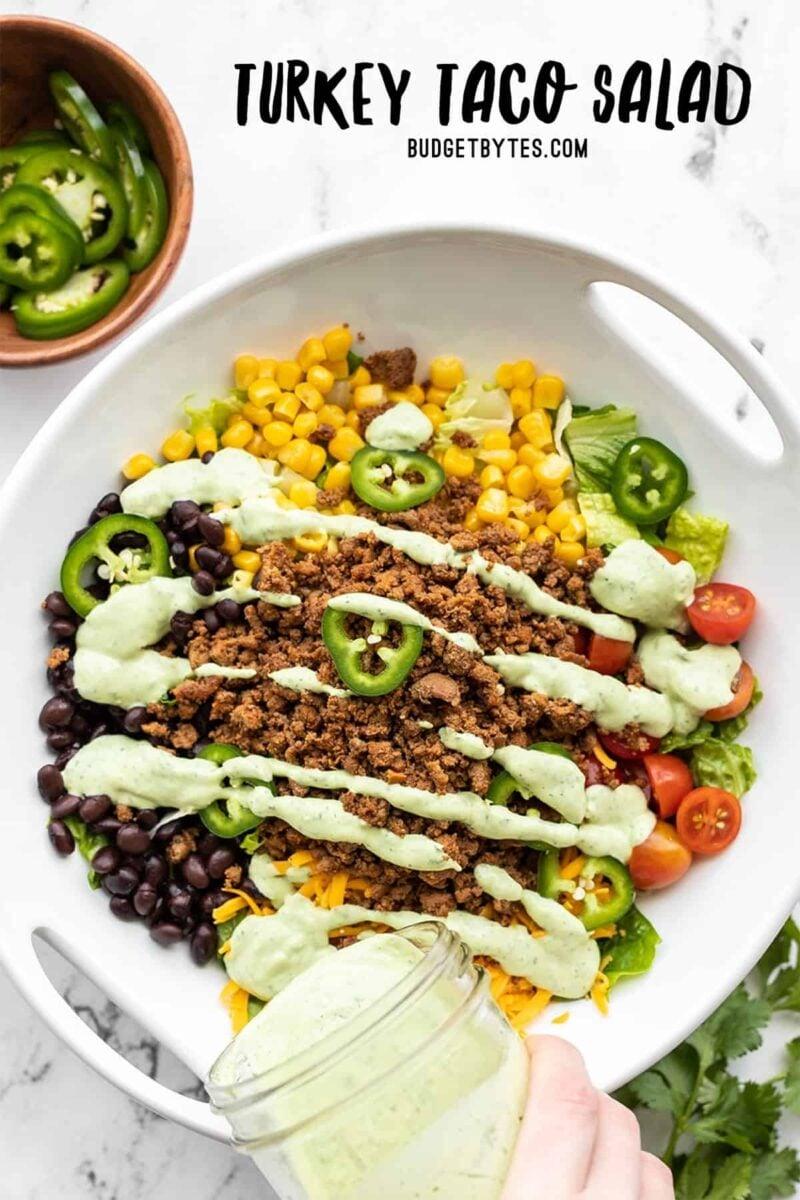 molho de abacate sendo servido sobre uma salada de taco de peru