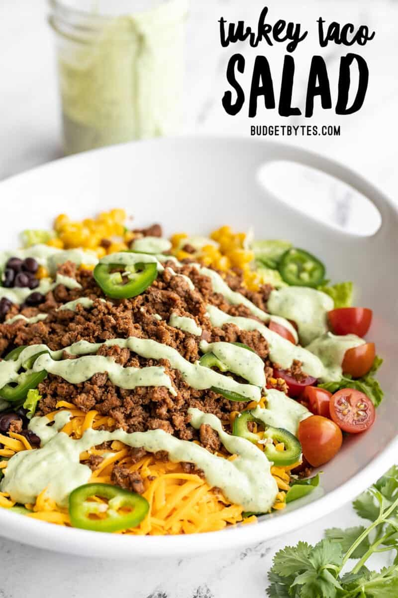 Side view of turkey taco salad in a serving bowl, title text at the top