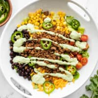 overhead view of turkey taco salad drizzled with creamy avocado dressing