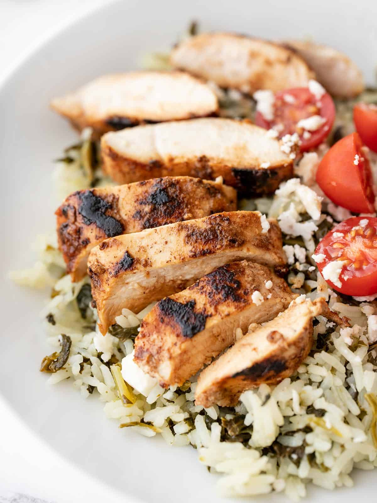Sliced yogurt marinated chicken on a bed of spinach rice with tomatoes