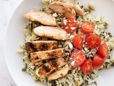 Sliced Yogurt Marinated chicken on a bed of spinach rice with tomatoes and feta