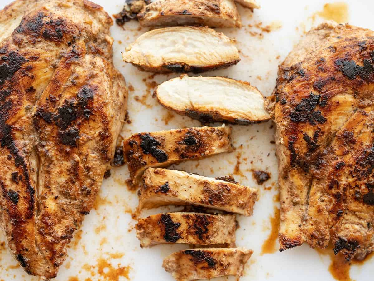 Sliced yogurt marinated chicken on a cutting board next to two whole cooked chicken breasts
