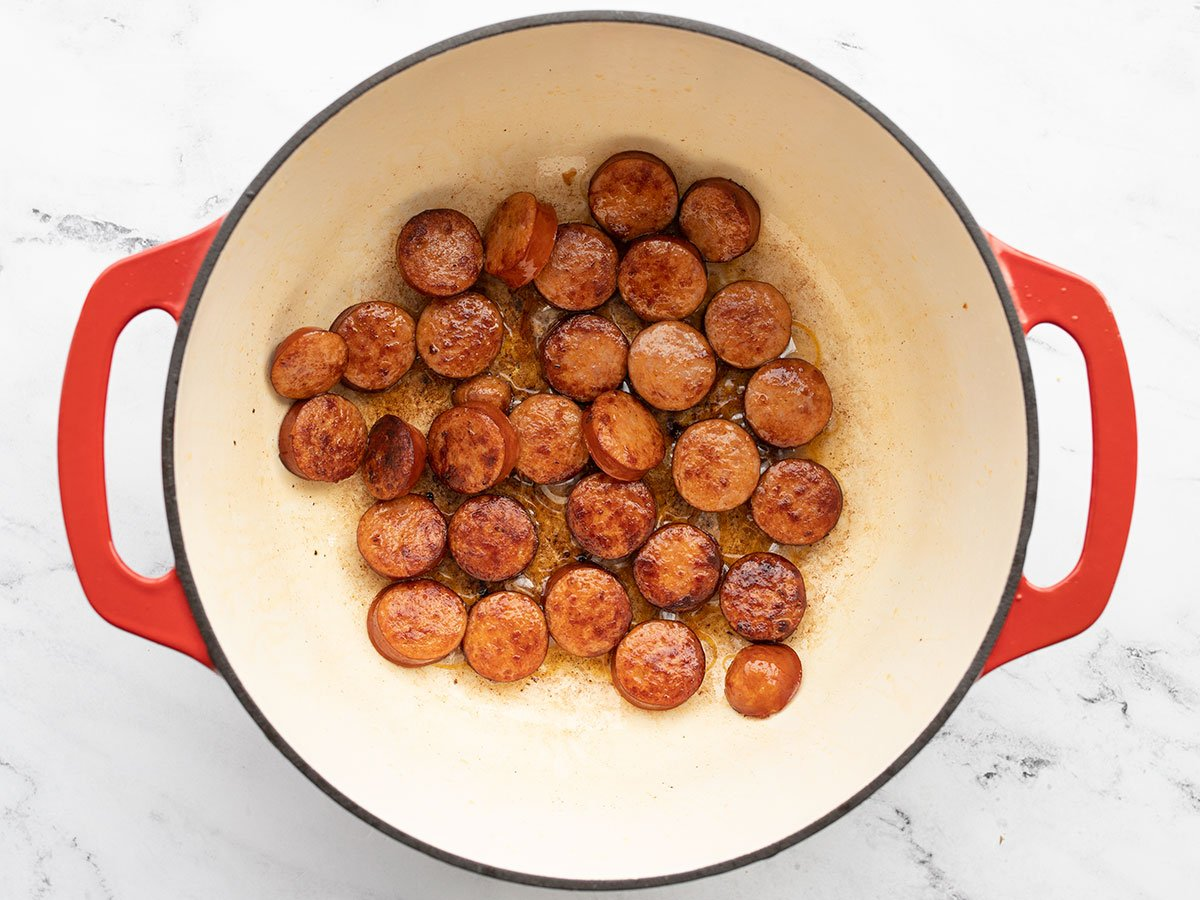 browned sausage rounds in a pot