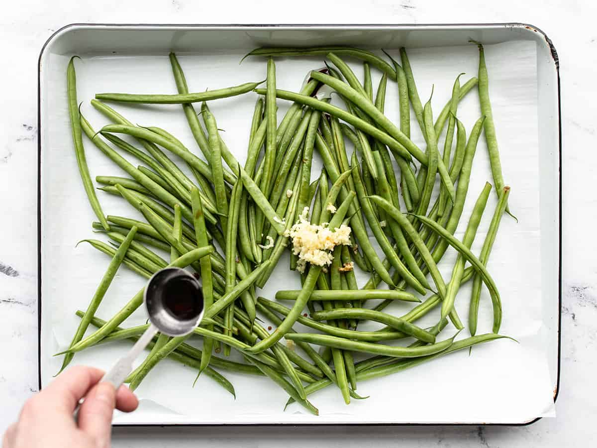 green beans and garlic on a baking sheet, soy sauce being drizzled over top