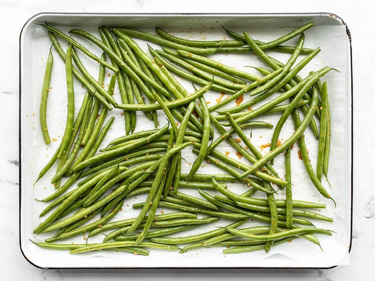 Seasoned green beans on the baking sheet