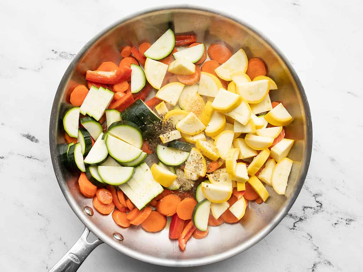 Zucchini, squash, bell pepper, and herbs added to the skillet