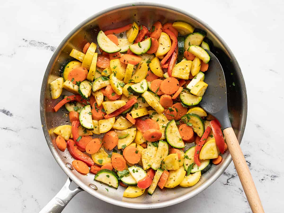 Finished sautéed vegetables in the skillet with a spatula