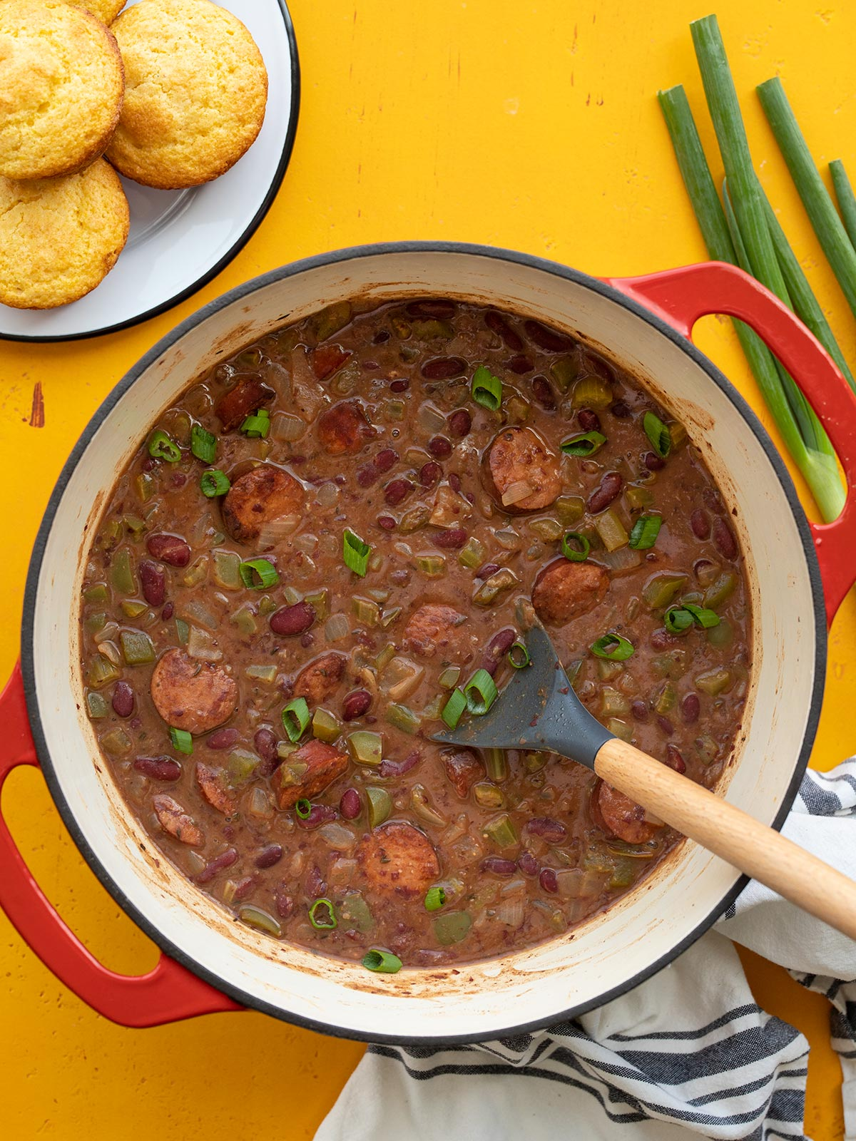 Overhead view of a pot of red beans with sausage, corn muffins on the side