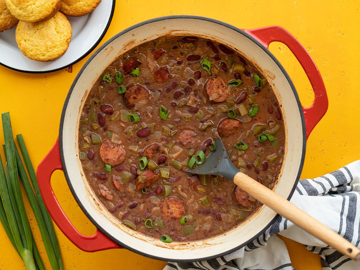 Overhead view of a pot of red beans with corn muffins on the side
