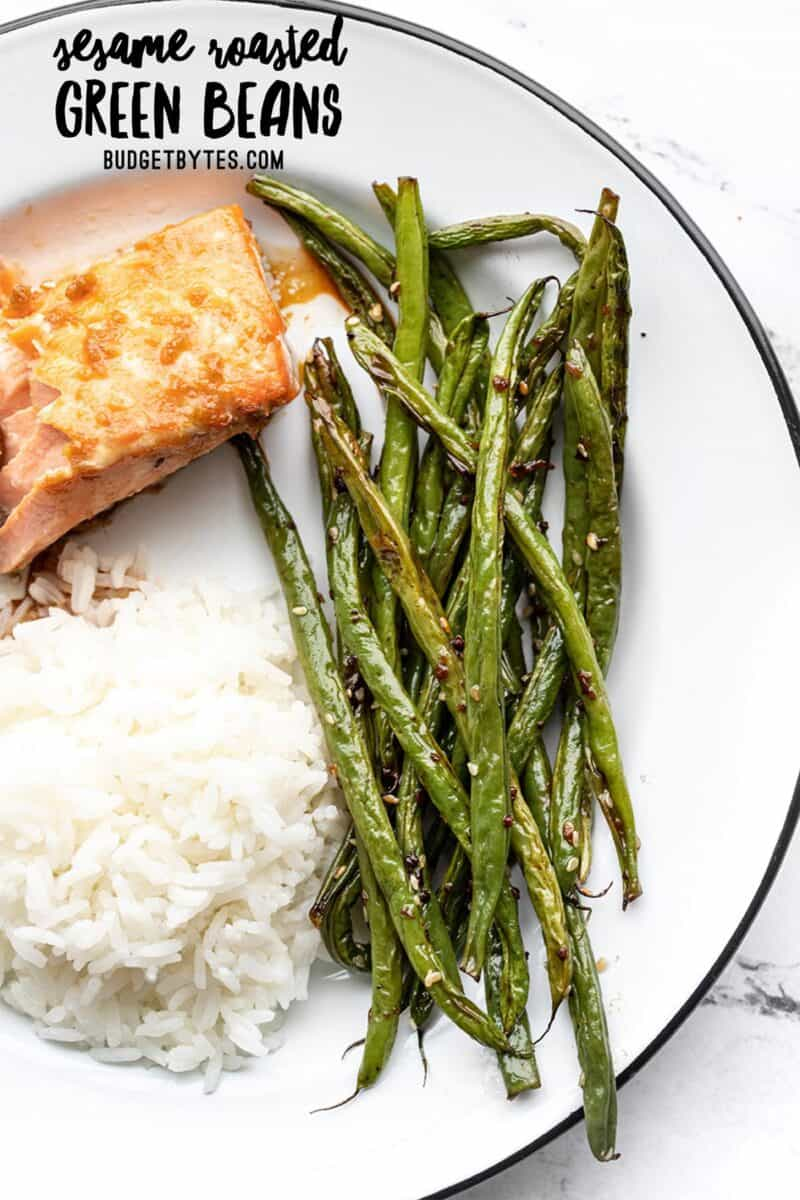 Sesame roasted green beans on a plate with salmon and rice, title text at the top