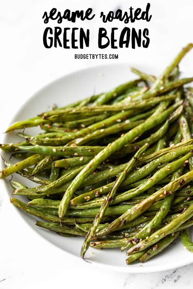 Side view of sesame roasted green beans in a bowl, title text at the top