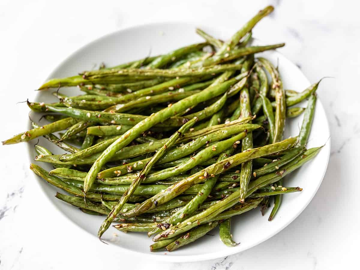 Side view of sesame roasted green beans in a shallow bowl.