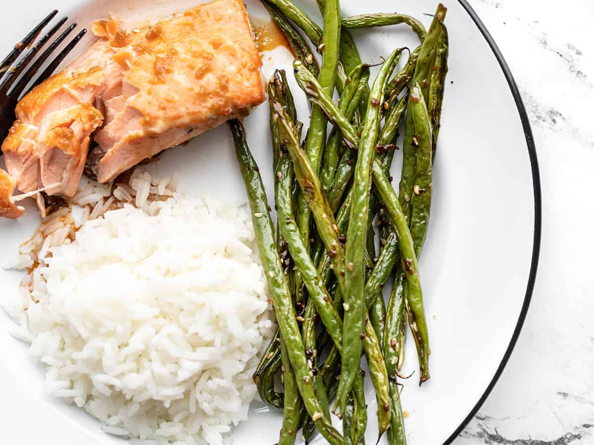 Sesame roasted green beans on a plate with salmon and rice