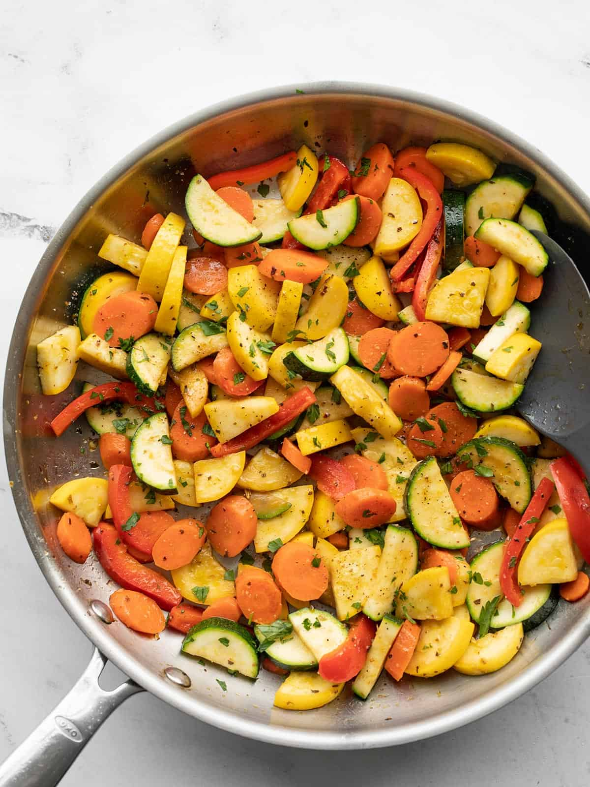 Sautéed vegetables in a skillet with a spatula