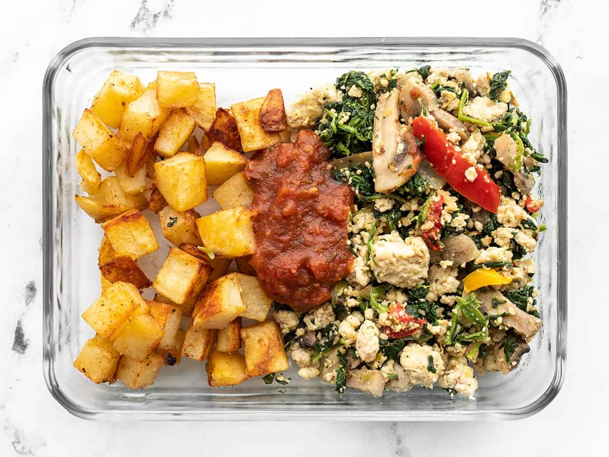 Vegetable tofu scramble in a glass meal prep box with roasted potatoes
