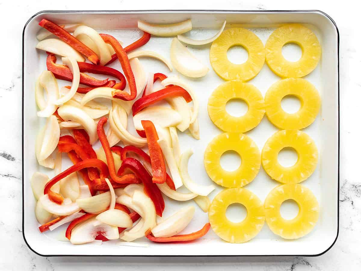 Pineapple slices on a baking sheet with the peppers and onions