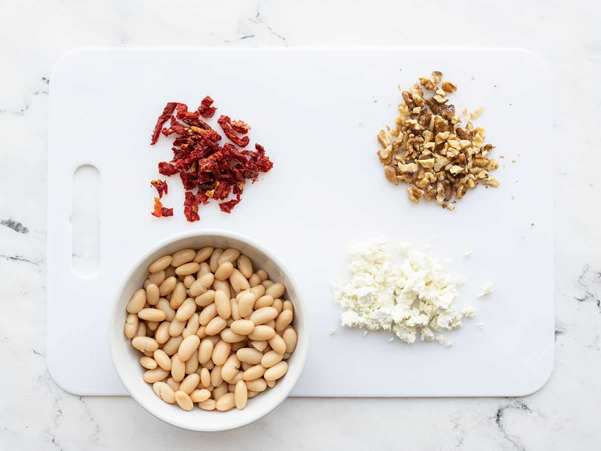 Sun dried tomatoes, walnuts, beans, and feta on a cutting board