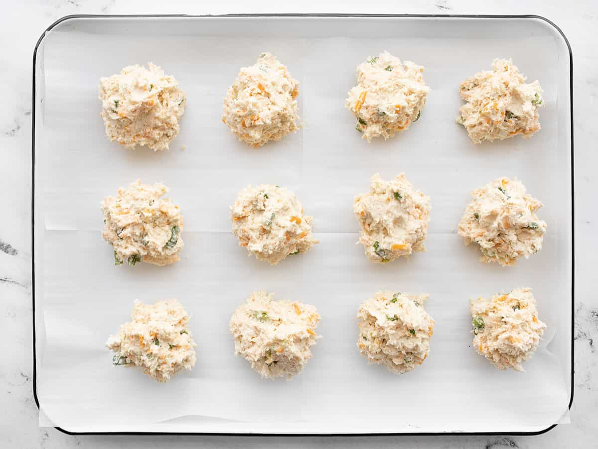 Biscuit batter dropped into clumps on the baking sheet