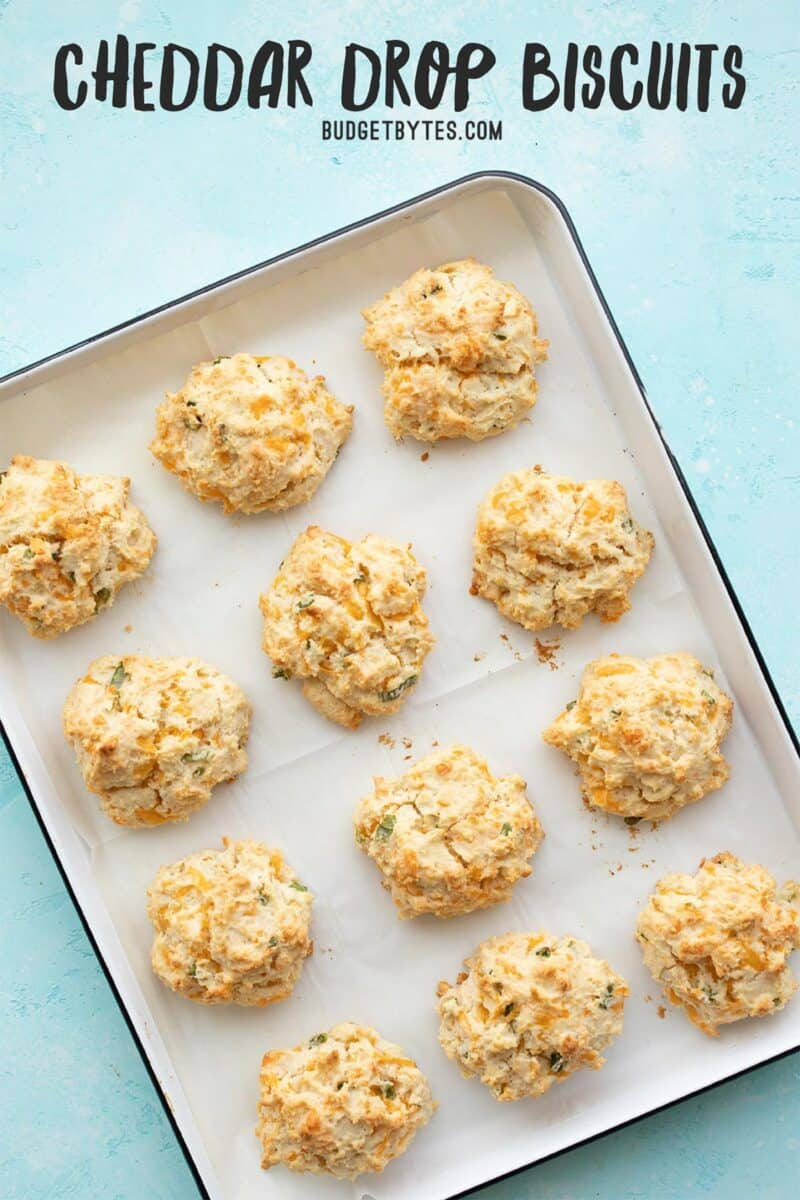 Cheddar drop biscuits on a baking sheet, title text at the top