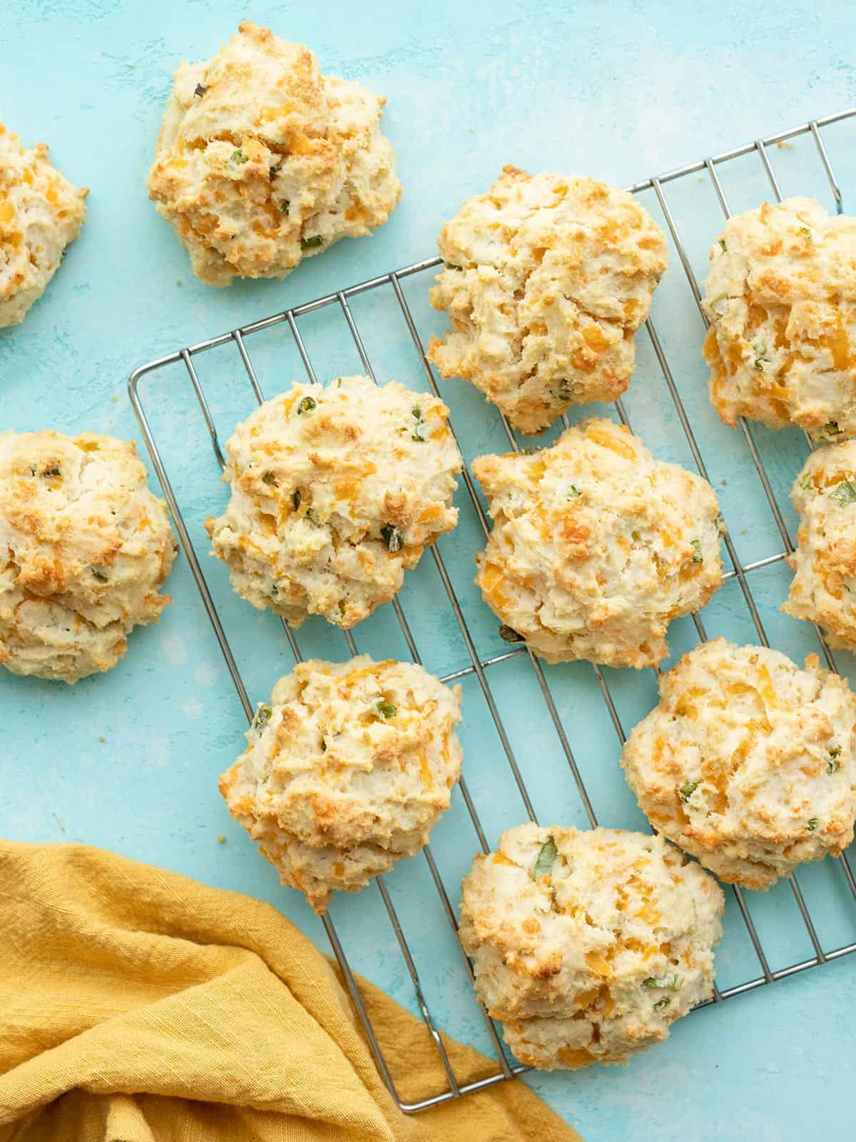 Cheddar drop biscuits on a wire cooling rack, on a blue surface
