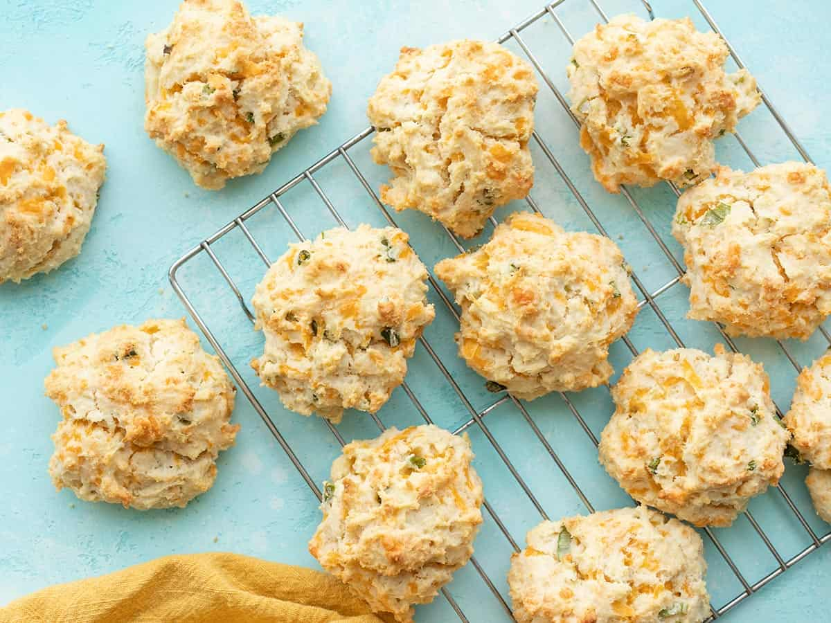 Cheddar drop biscuits on a wire cooling rack against a blue background