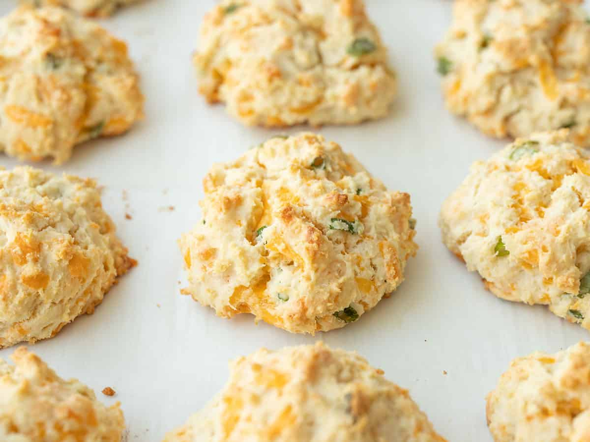 Side view of baked cheddar biscuits on the baking sheet