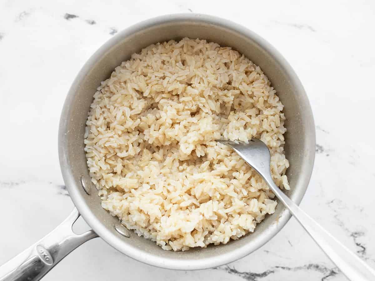 Cooked brown rice in a pot being fluffed with a fork