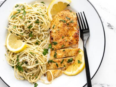 A sliced piece of lemon pepper chicken on a plate with pasta.