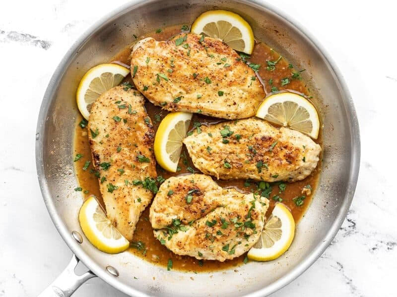 Overhead view of lemon pepper chicken in the skillet with lemon slices