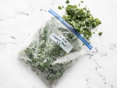 A freezer bag full of kale spilling out onto a marble surface