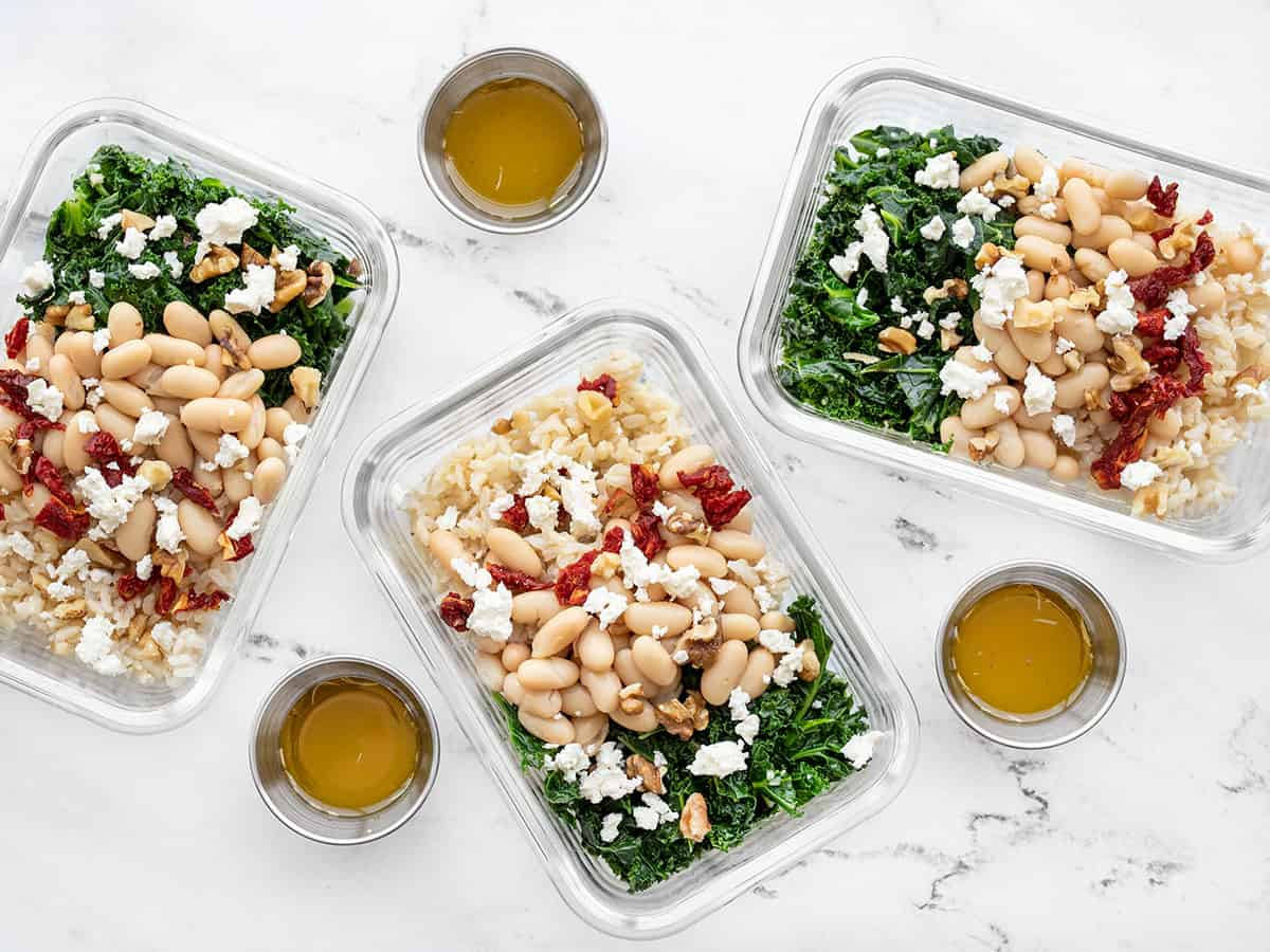 three glass meal prep containers filled with kale and white bean power bowls