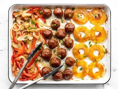 Overhead view of sheet pan with bbq meatballs, pineapple, peppers, and onions, tongs on the side