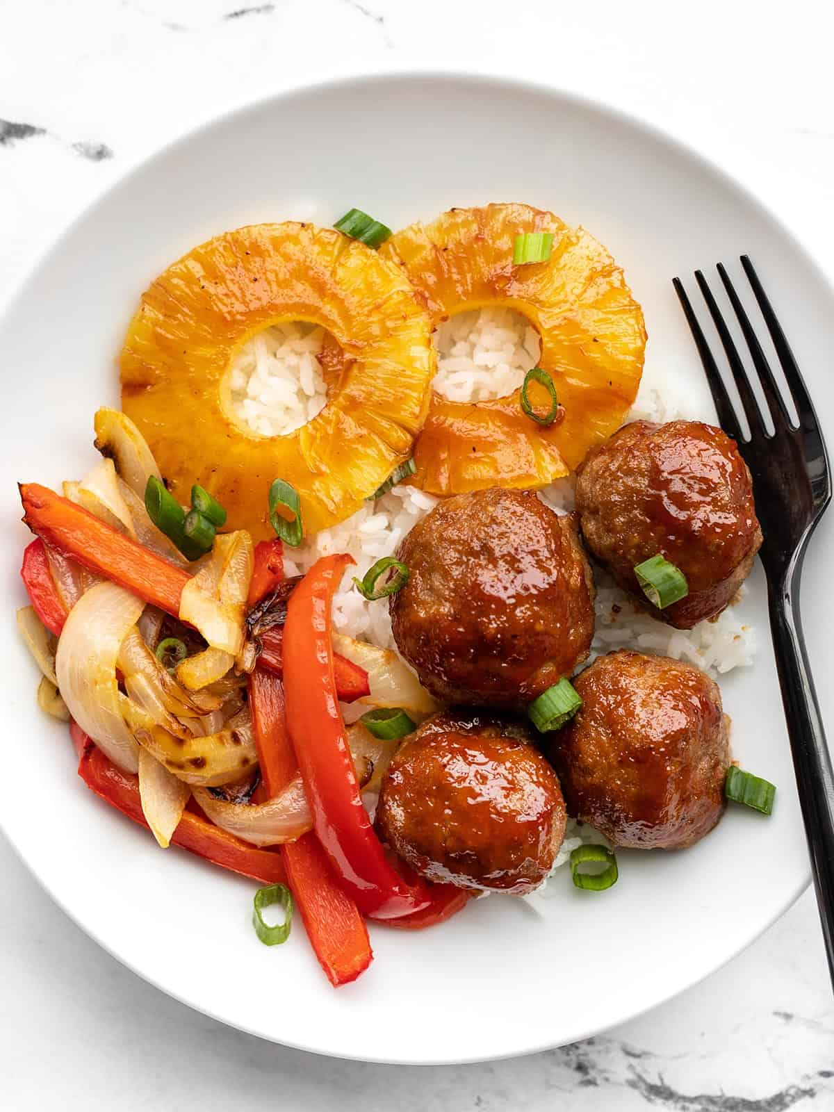 A bowl with rice, sheet pan BBQ meatballs, roasted peppers and onions, and pineapple slices.