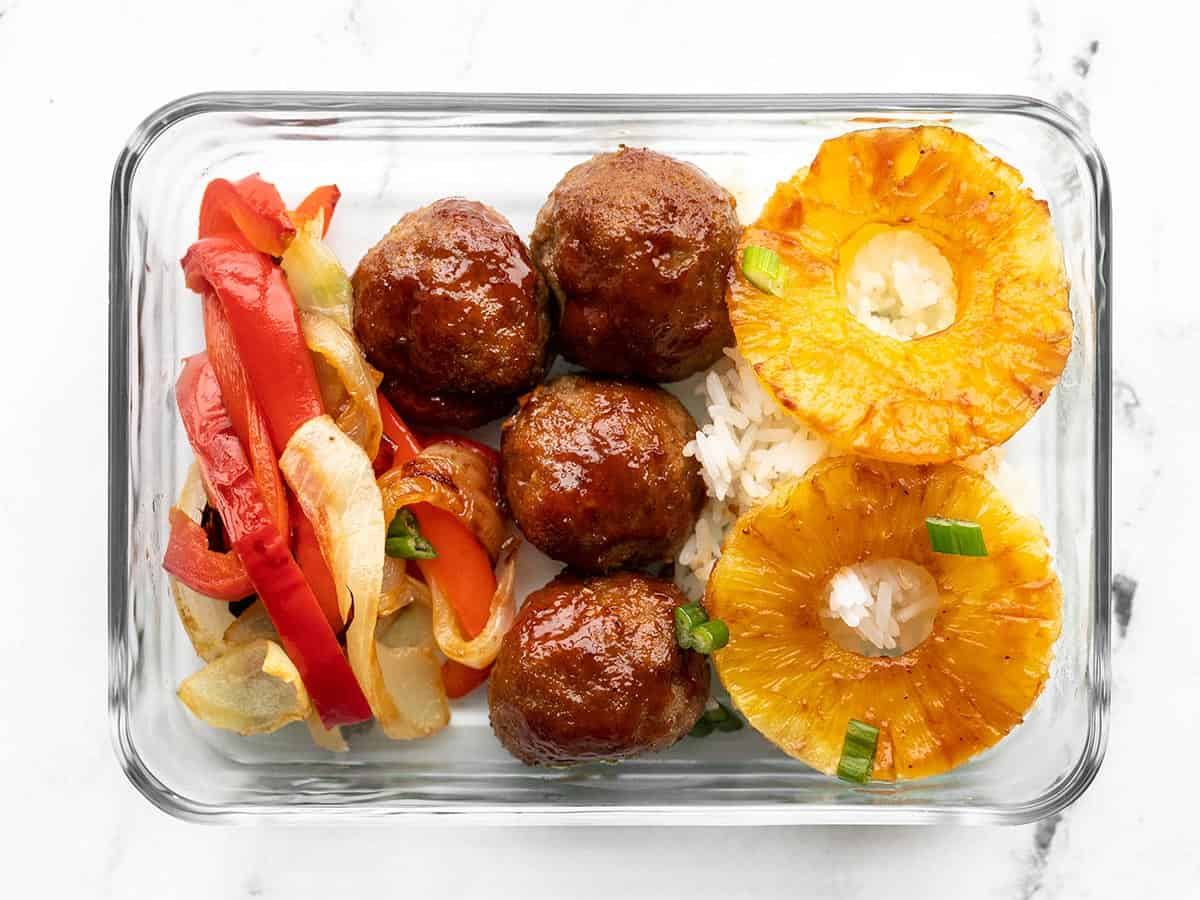 Glass meal prep container with rice, bbq meatballs, peppers, onions, and pineapple
