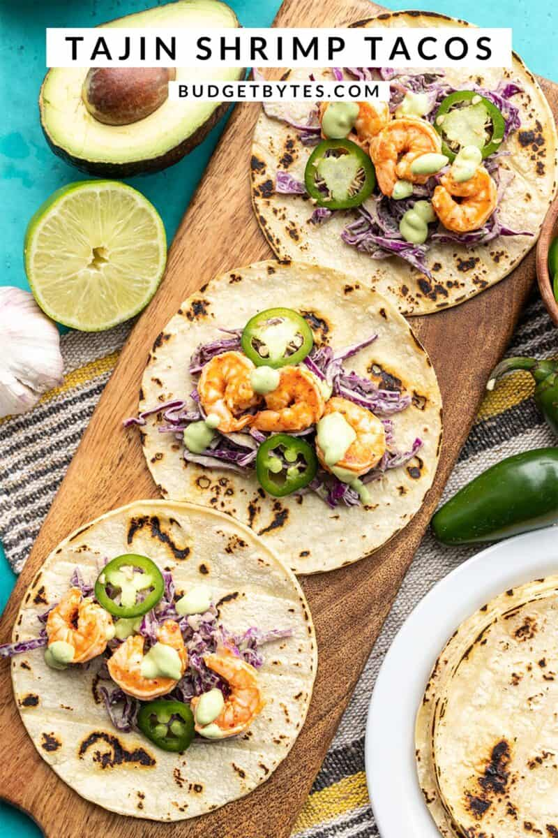 Three open faced Tajín Shrimp Tacos on a wooden board, title text at the top