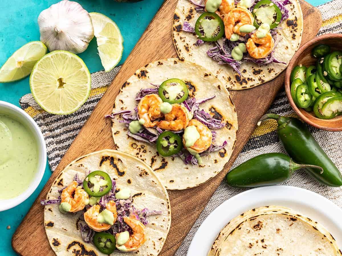 Three Tajín Shrimp Tacos open faced on a wooden board