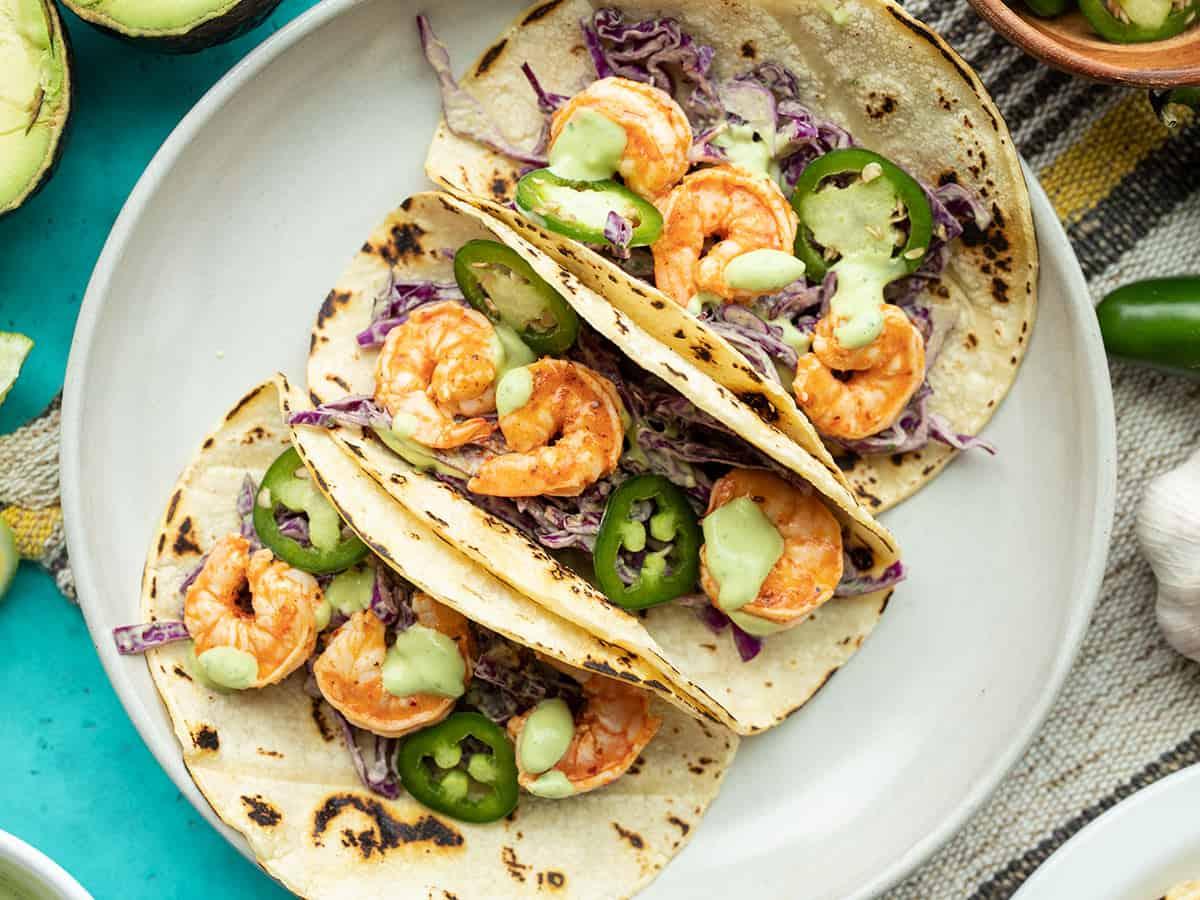 Close up of three Tajín Shrimp Tacos on a plate