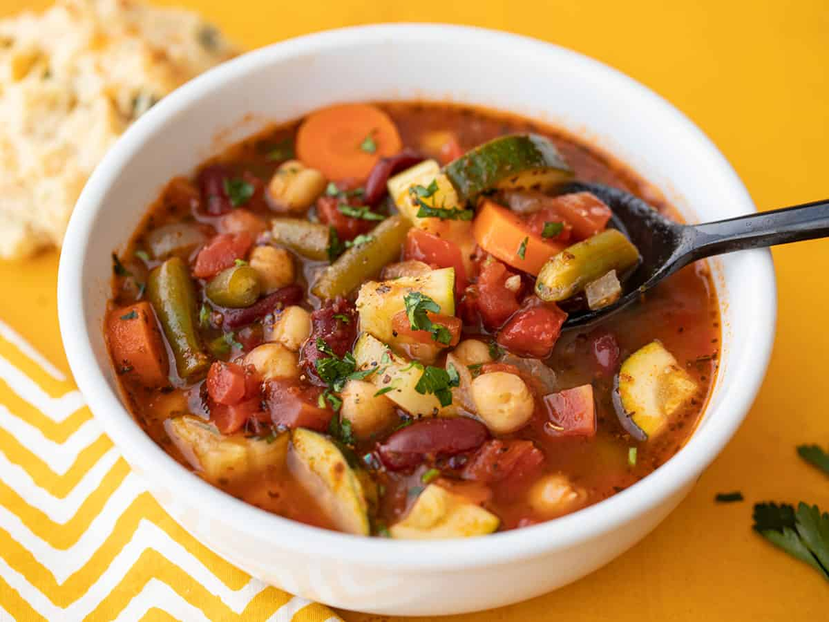 Front view of a bowl full of vegetarian minestrone with a spoon lifting a bite